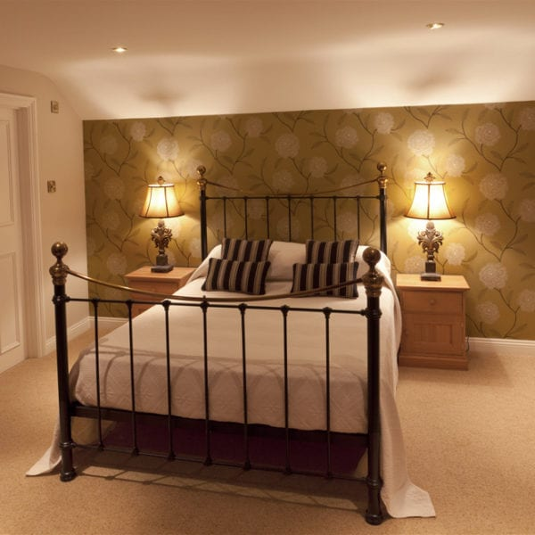 a picture of a dark cream bedroom with gold and cream plant feature wall, two bright ornament lamps on bedside cabinets