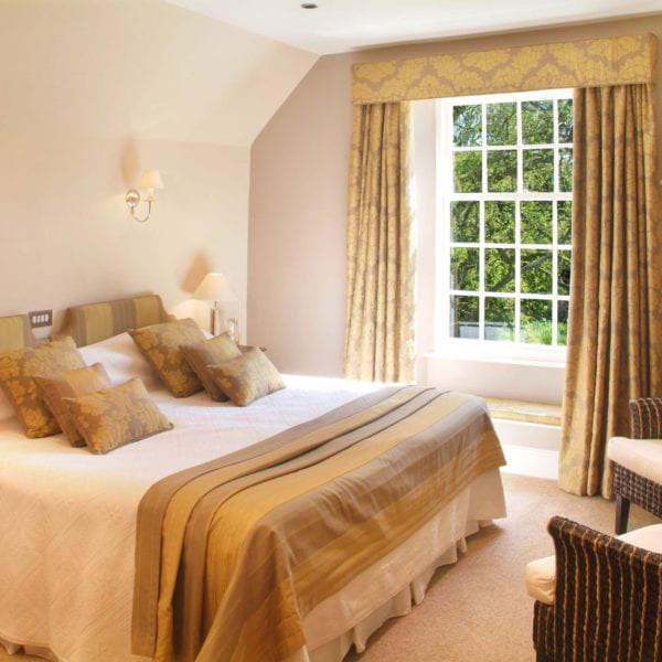 a picture of a cream bedroom, with gold and light brown accents in curtains, cushions and headboards, with a view of green trees out of the window