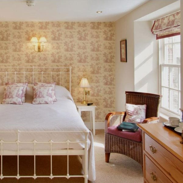 a picture of a cream bedroom with a white bed, a red and cream wallpaper with red and cream patterned cushions