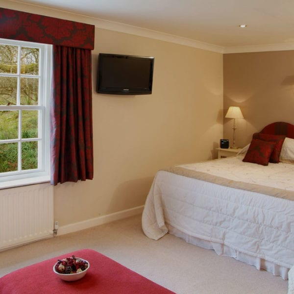 va picture of a cream room with dark red accent curtains, cushions on the bed and red accent headboard