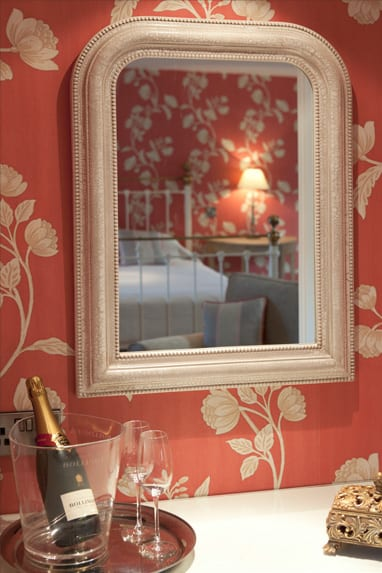 A picture of a mirror reflecting a bedroom view, red wallpaper with cream flowers and a bottle of champagne