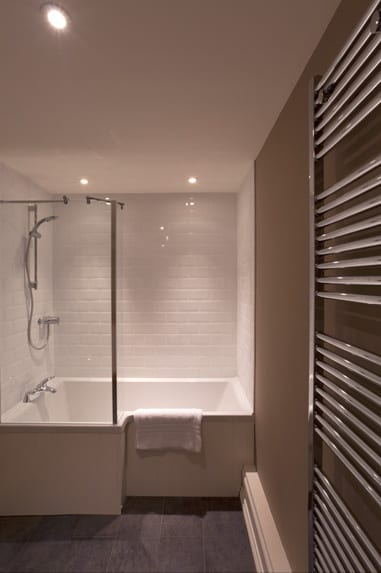 a picture of a white brick bathroom, with a wide set white square bath, a white towel and an overhead silver coloured shower