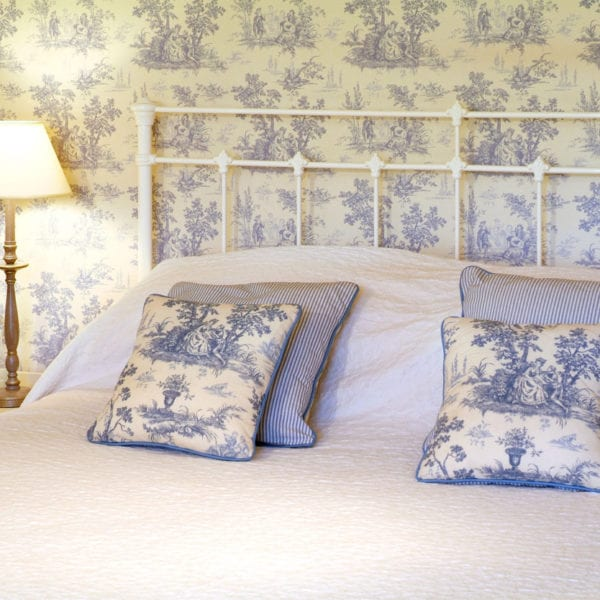 a picture of a bed with blue and blue and white patterned pillows next to a lamp