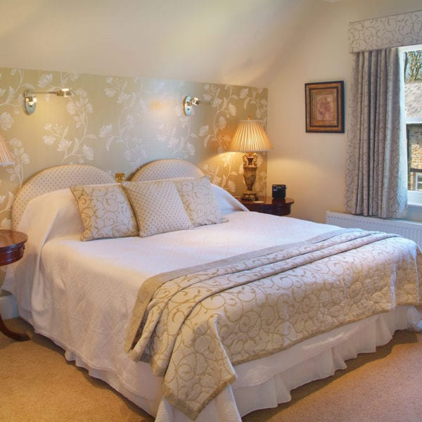 a picture of a cream bedroom with a pale green white flower feature wall, with a view of a cottage out of the window