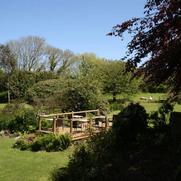 a picture of large garden with a wooden patio centred, with garden furniture