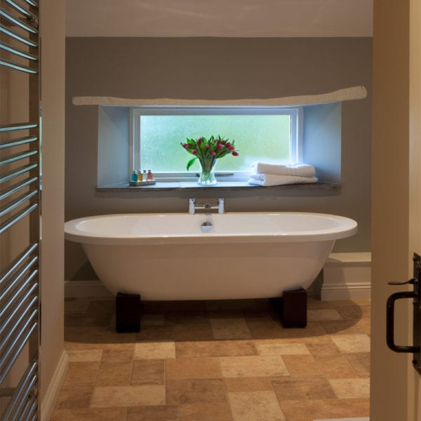 A picture of a large freestanding bath tub on dark brown stands, with a vase of pink tulips on the above shelf