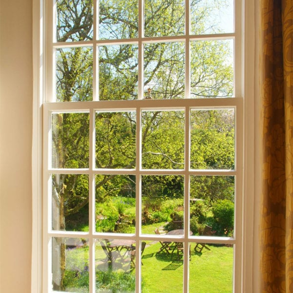 a picture of a window with a view of the garden, trees and garden furniture outside