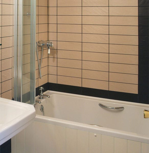 a bathroom with beige tiles and a stand over shower