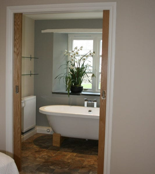 a picture of a bathroom with a white freestanding bath with a vase of lilies