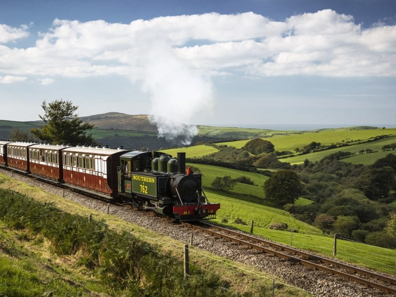 a picture of a steam train rolling through the countryside from woody bay station
