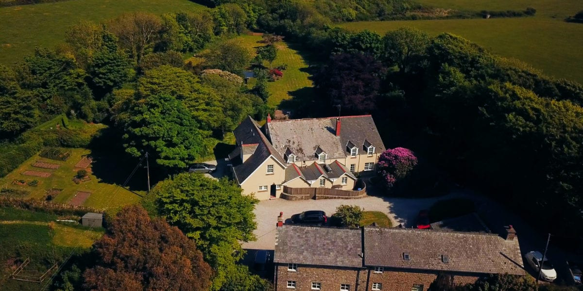 an aerial view of a cream building the old rectory hotel and surrounding garden, trees and allotment