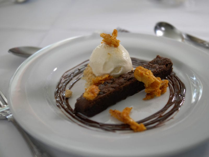 a picture of a strip of brownie cake toped with honeycomb, ice cream and surrounded by chocolate sauce