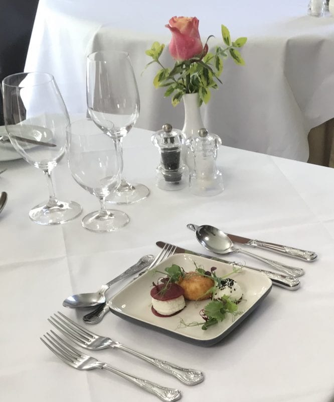 a picture of a set table with a plate of food and a vase with a pink tulip