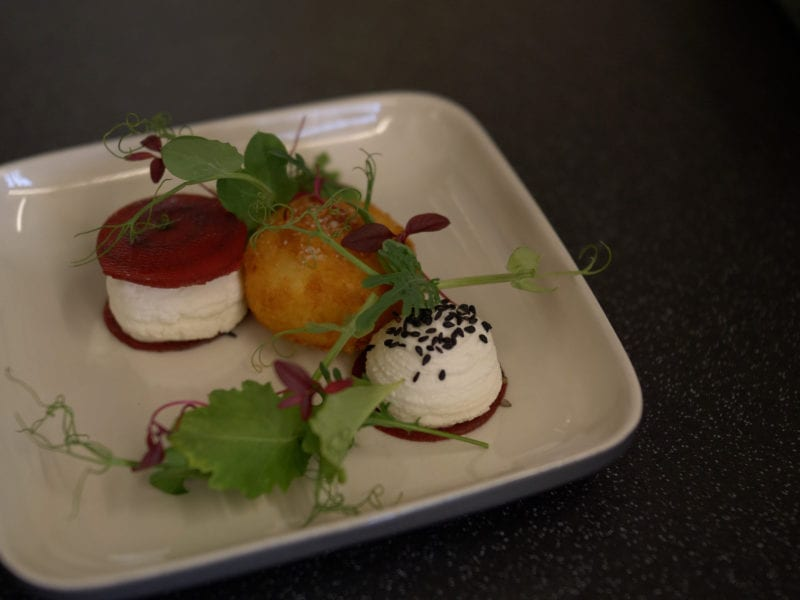 a picture of beetroot and cheese curd with a deep fried ball and salad garnish