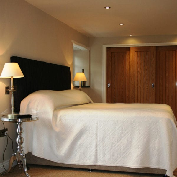 a picture of a cream bedroom with brown wooden doors and a light brown carpet