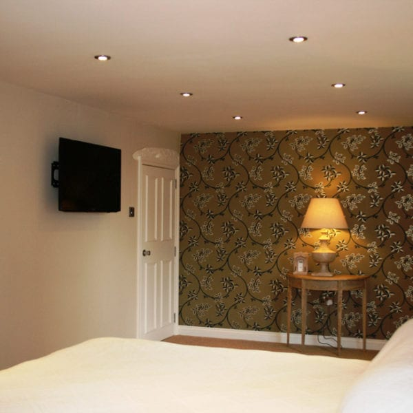 a picture of a cream bedroom with a gold and cream flower feature wall