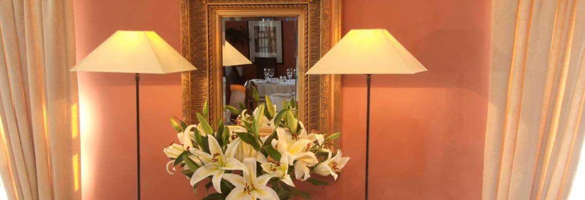 a picture of an orange dining room with cream curtains, two lamps, a wooden framed mirror and a vase of white lilies