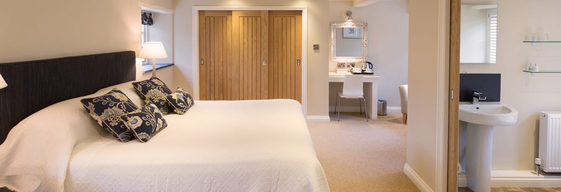 a picture of a cream bedroom with wooden doors and blue plant patterned cushions on the bed