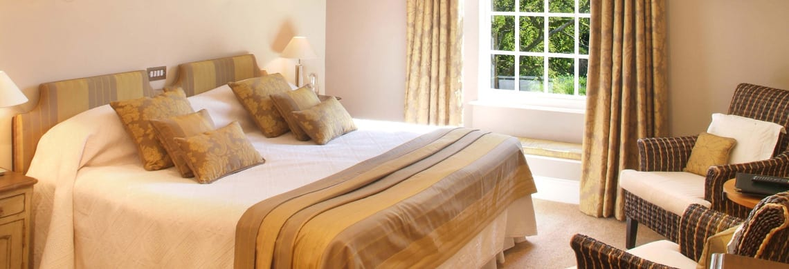 a picture of a cream bedroom with gold accessories such as cushions, curtains and headboards