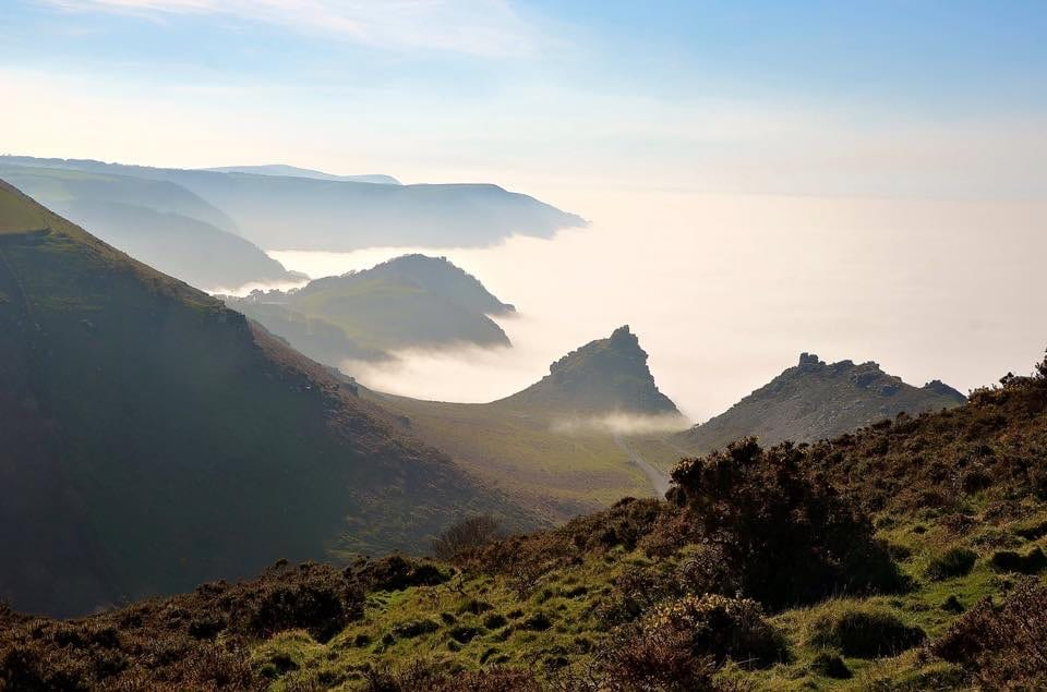 a picture of rocky green covered hills over looking the sea with clouds hovering over