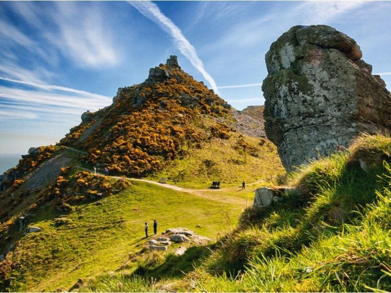 a picture of large cliffs and grass covered rocks, Valley of Rocks