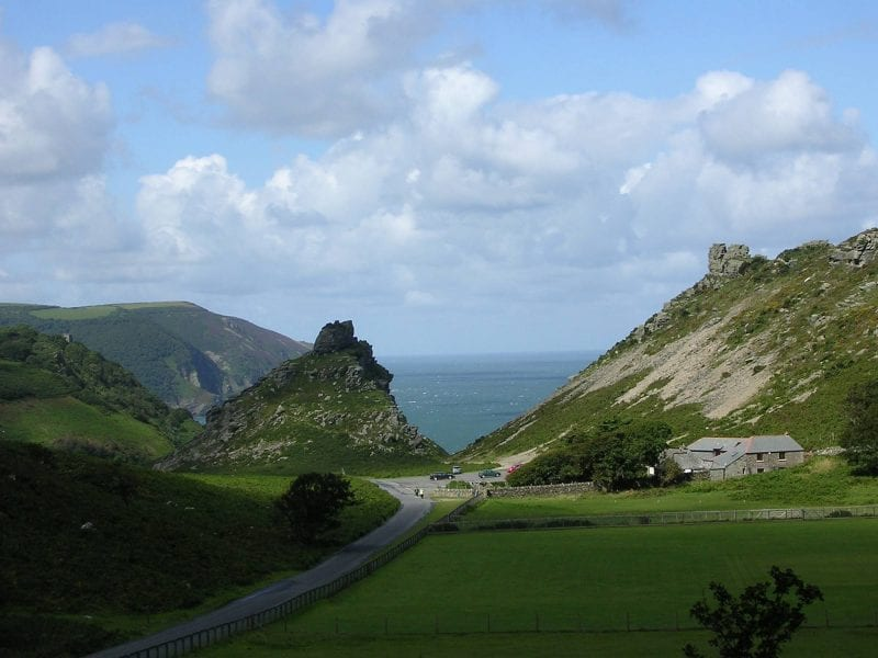 a picture of large rocky hills covered in grass with a pathway leading down on the blue sea