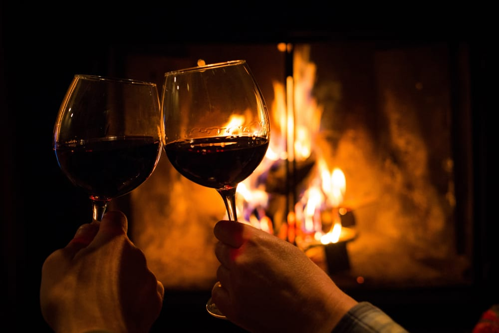 a picture of two people clinking two glasses of red wine together infront of a fire