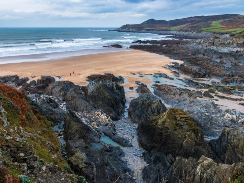 A picture of Barricane beach, colourful rocks surrounding a sandy beach with the sea in the background