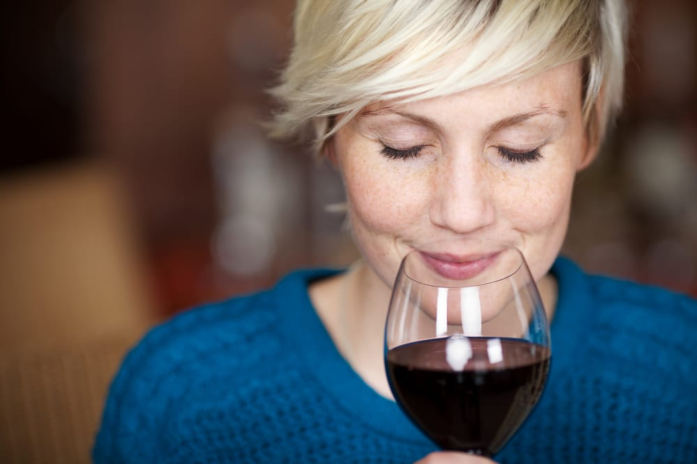 Lady smelling a glass of red wine