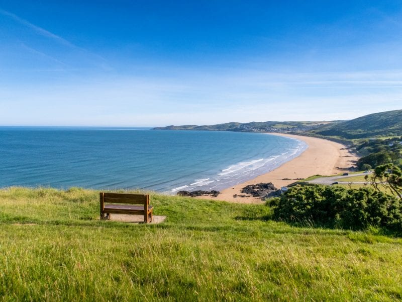 A picture of a landscape at Putsborough with a bench on the grass, over looking the coast and hills