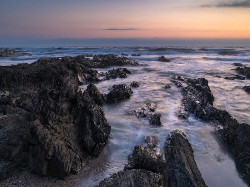 a picture of the flowing sea amongst slate grey rocks with a sunset in the background
