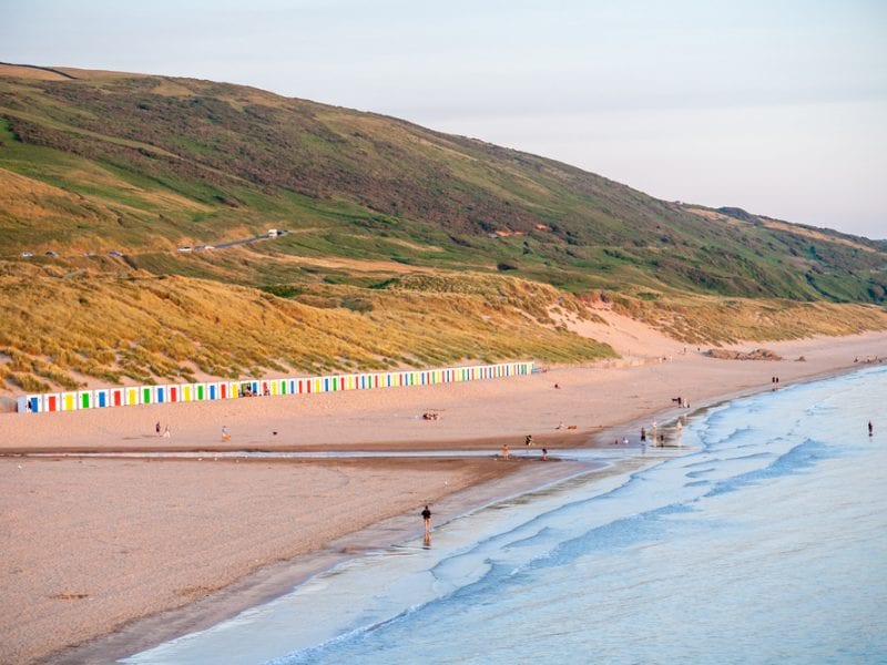 a picture of Woolacombe, landscape of green hills, colourful beach huts, sand and the light blue sea